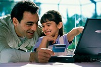 Father and his daughter in front of a laptop holding a credit card