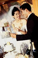 Newlywed couple standing near a wedding cake and toasting with glasses of champagne
