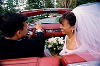 Newlywed couple talking to each other in a convertible car