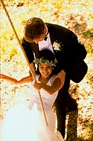 Portrait of newlywed young woman sitting on a swing with a her groom pushing her