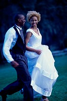 Side profile of a newlywed couple running on a lawn