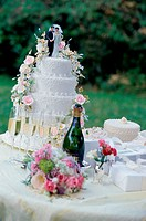 Wedding cake with a bouquet of flowers and a bottle of champagne