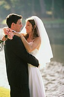 Newlywed couple embracing near a lake