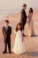 Newlywed couple standing on the beach with a flower girl and a ring bearer