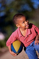 Boy kneeling with a rugby ball