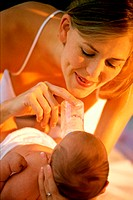 Close-up of a mother feeding her baby girl with a baby bottle