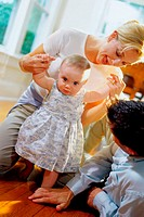 Parents helping their baby girl learn how to walk (thumbnail)