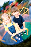 Portrait of a boy and a girl standing on a merry-go-round