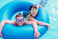 High angle view of a boy and a girl in an inflatable ring in a swimming pool