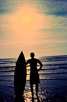 Silhouette of a man holding a surfboard standing on the beach