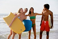 Two teenage couples standing on the beach holding boogie boards