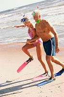 Senior couple walking on the beach wearing snorkeling gear