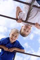 Low angle view of two boys playing on monkey bars