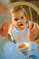 Grandfather feeding his granddaughter
