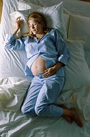 High angle view of a pregnant woman sleeping on a bed