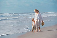 Mother walking with her daughter on the beach