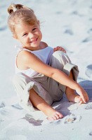 Portrait of a girl playing in the sand on the beach