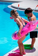 Boy and a girl standing at the poolside wearing snorkels and flippers