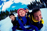 Close-up of two boys and two girls riding on a sled