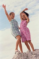 Two girls standing on the beach with their arms raised