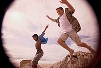 Side profile of two boys jumping on the beach