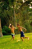 Two boys playing in a water sprinkler