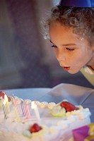 Girl blowing candles on her birthday cake