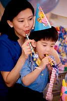 Boy wearing a birthday cap blowing a party horn blower with his mother
