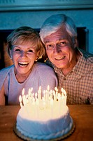 Senior couple blowing out candles on a cake