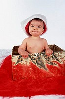 Portrait of a baby boy sitting in a box wearing a Christmas hat