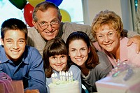Portrait of grandparents and their grandchildren in front of a cake