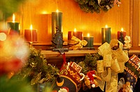 Lit candles and Christmas decorations on a mantelpiece