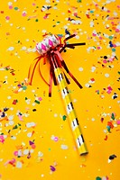 Close-up of a party horn blower and confetti