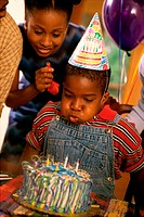 Boy blowing out candles on his birthday cake