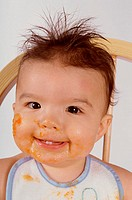 Portrait of a baby boy smiling with food on his face