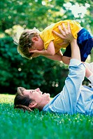 Side profile of a mother lying on a lawn lifting her son