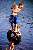Two boys playing on a tire swing