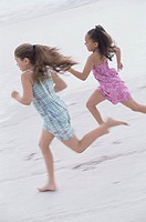 Side profile of two girls running on the beach