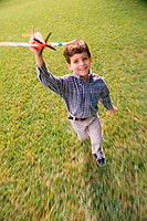Portrait of a boy running with a toy airplane