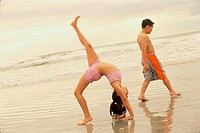 Side profile of a girl bending over backwards and a boy walking behind her