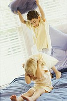 Boy and a girl having a pillow fight on a bed