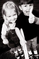 Portrait of a boy standing with a girl showing thumbs up sign