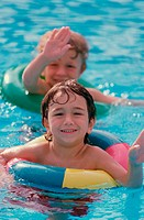 Two boys wearing inner tubes in a swimming pool