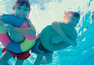 Low angle view of a boy and a girl lying on inflatable rings in a swimming pool