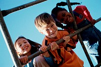 Portrait of a boy and two girls on monkey bars