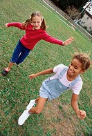 High angle view of two girls playing together on a lawn
