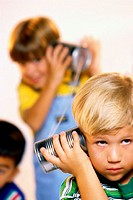 Two boys playing with tin can phone