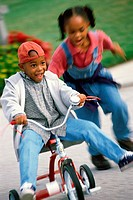 Boy and a girl playing on a tricycle