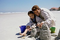 Father and his daughter making sand castles on the beach