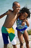 Close-up of a girl and a boy holding each other on the beach